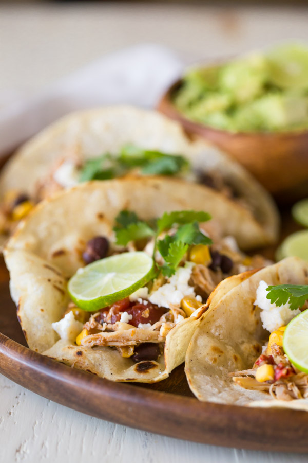 Three Crockpot Salsa Chicken Tacos arranged on a wood serving plate, with a small bowl of sliced avocado.