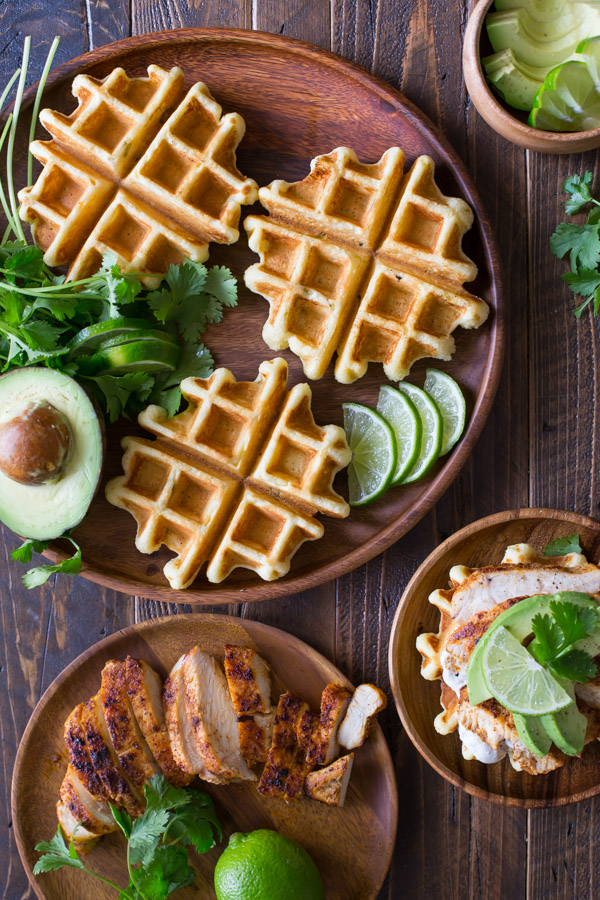 A Green Chile Chicken Waffletada assembled on a wood plate, sitting next to a large wood plate with mini cornbread waffles, lime slices, half an avocado and cilantro, a small wood bowl of avocado slices, and another wood plate with the grilled chicken on it.