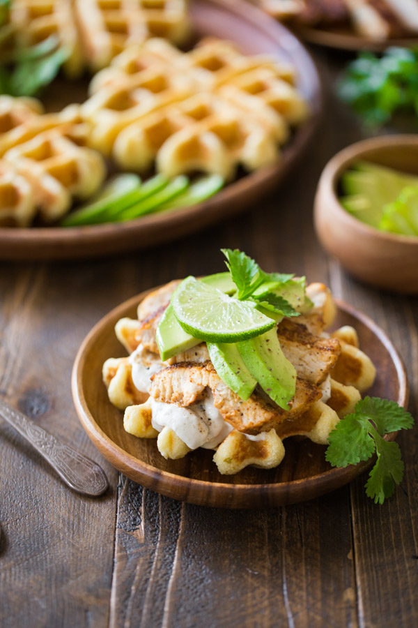 A Green Chile Chicken Waffletada assembled on a wood plate, with a large wood plate with mini cornbread waffles in the background.