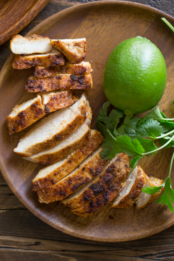 A wood plate with the sliced grilled chicken for the Green Chile Chicken Waffletada, along with a whole lime and some cilantro.