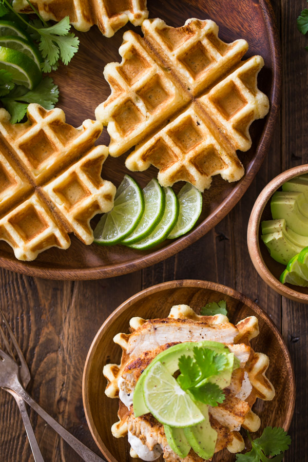 A Green Chile Chicken Waffletada assembled on a wood plate, sitting next to a large wood plate with mini cornbread waffles, lime slices and cilantro, and a small wood bowl of avocado slices.