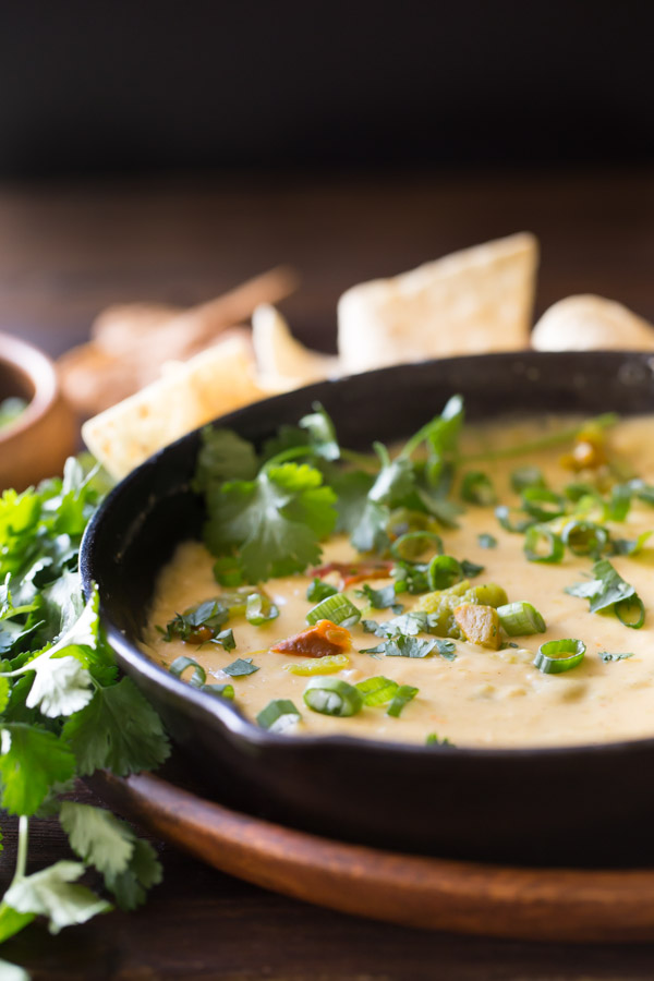 Hatch Green Chile Queso in a small cast iron skillet, garnished with green chiles, chopped cilantro, and green onions , sitting on a large wood plate with tortilla chips and a bundle of cilantro.