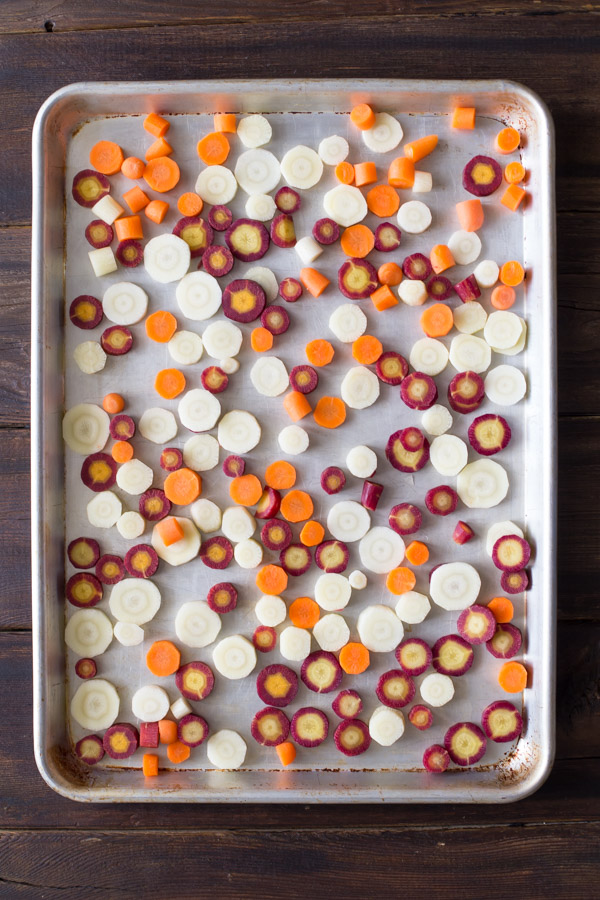 Purple, white and orange carrot slices on a baking sheet before roasting.