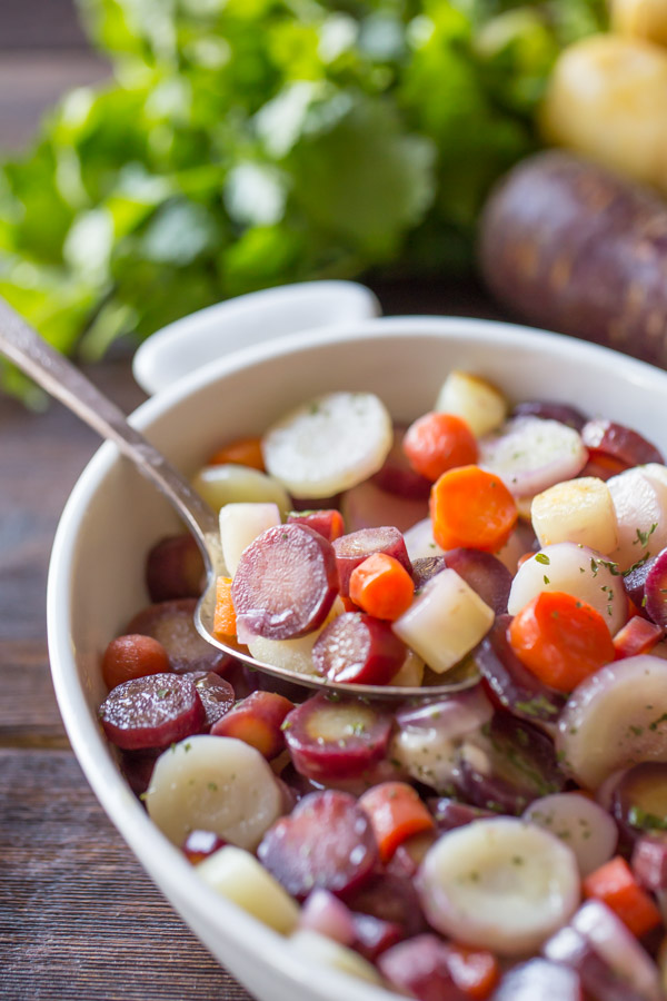 Honey Roasted Rainbow Carrots in a serving dish with a serving spoon in it.