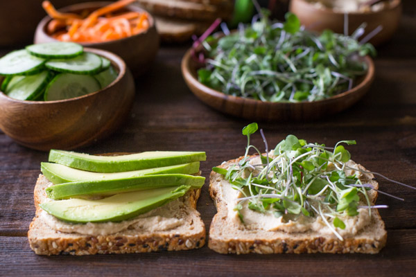 A Power Veggie Sandwich being assembled with roasted garlic hummus and slices of avocado on one slice of bread and roasted garlic hummus and micro greens on the other, with more ingredients for the sandwich in the background.