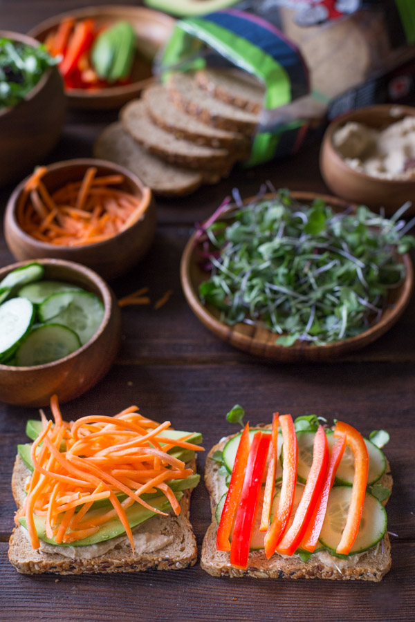 A Power Veggie Sandwich being assembled on two slices of bread, with all the ingredients in the background.