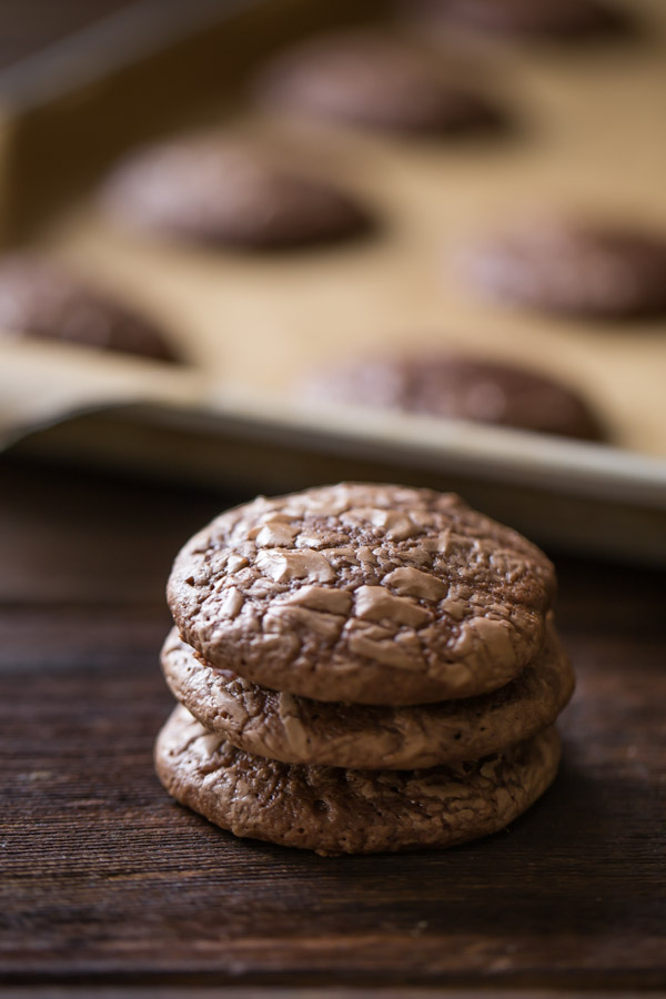 A stack of three Soft and Chewy Brownie Cookies, with more cookies on a parchment paper lined baking sheet in the background.