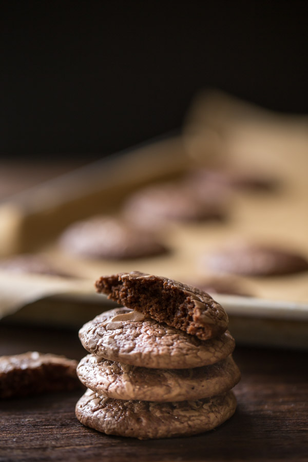 A stack of three Soft and Chewy Brownie Cookies with a half of a cookie on top, and more cookies on a parchment paper lined baking sheet in the background.