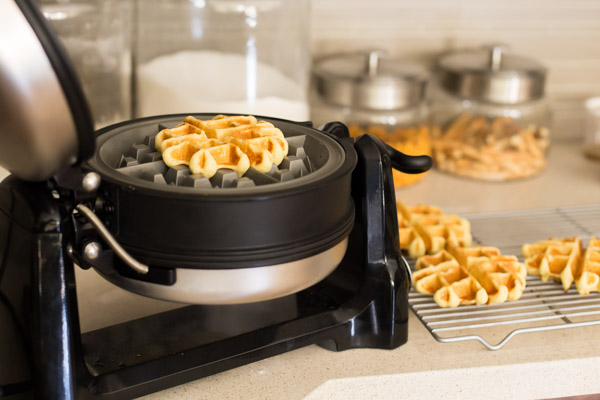 KitchenAid Waffle Baker with the lid open and a cooked mini cornbread waffle inside, with more waffles on a cooling rack next to it.