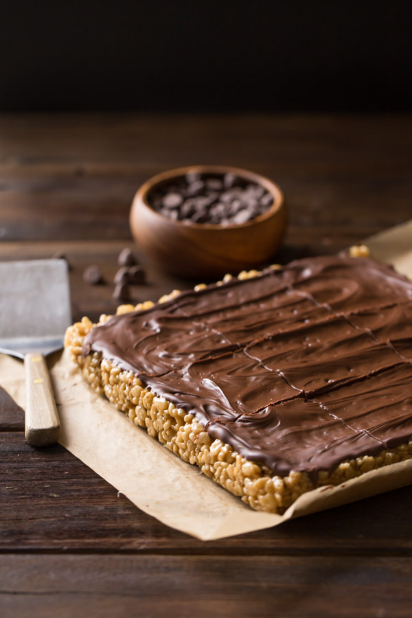 Chocolate Peanut Butter Rice Krispie Bars on a piece of parchment paper, with a small bowl of chocolate chips and a spatula next to them.