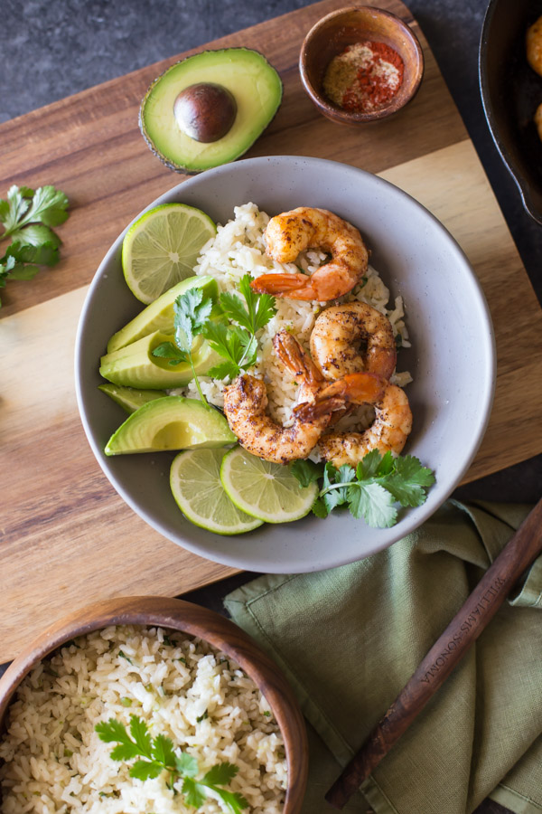 Cilantro Lime Rice Shrimp Bowl garnished with lime slices, avocado slices and fresh cilantro, sitting on a wood board with a small bowl of spices and a half of an avocado, and a wood bowl of Cilantro Lime Rice next to the board.