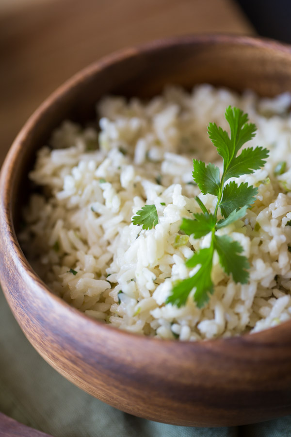 A wood bowl of Cilantro Lime Rice garnished with some fresh cilantro.