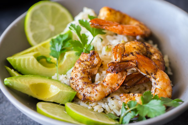 Cilantro Lime Rice Shrimp Bowl garnished with lime slices, avocado slices and fresh cilantro.
