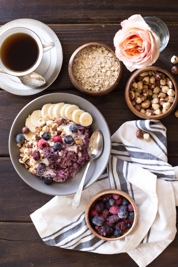 Triple Berry Oatmeal Breakfast Bowl topped with vanilla yogurt, crushed hazelnuts, sliced banana, and berries, with a cup of coffee, a bowl of oats, a bowl of hazelnuts and a bowl of berries next to the Triple Berry Oatmeal Breakfast Bowl.