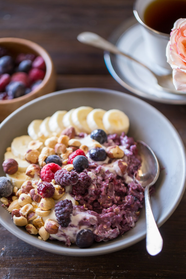 Triple Berry Oatmeal Breakfast Bowl topped with vanilla yogurt, crushed hazelnuts, sliced banana, and berries, with a small bowl of berries and a cup of coffee in the background.