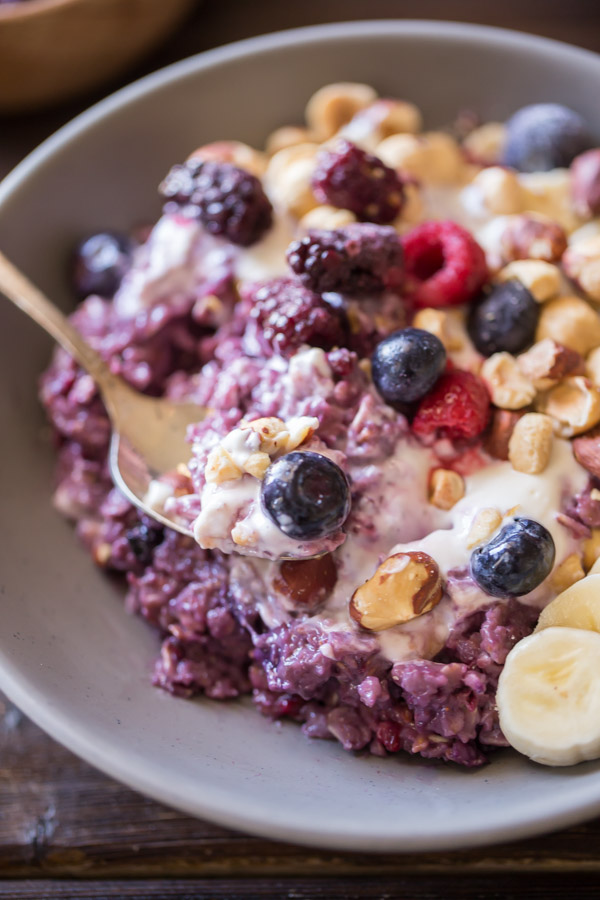 Triple Berry Oatmeal Breakfast Bowl topped with vanilla yogurt, crushed hazelnuts, sliced banana, and berries.