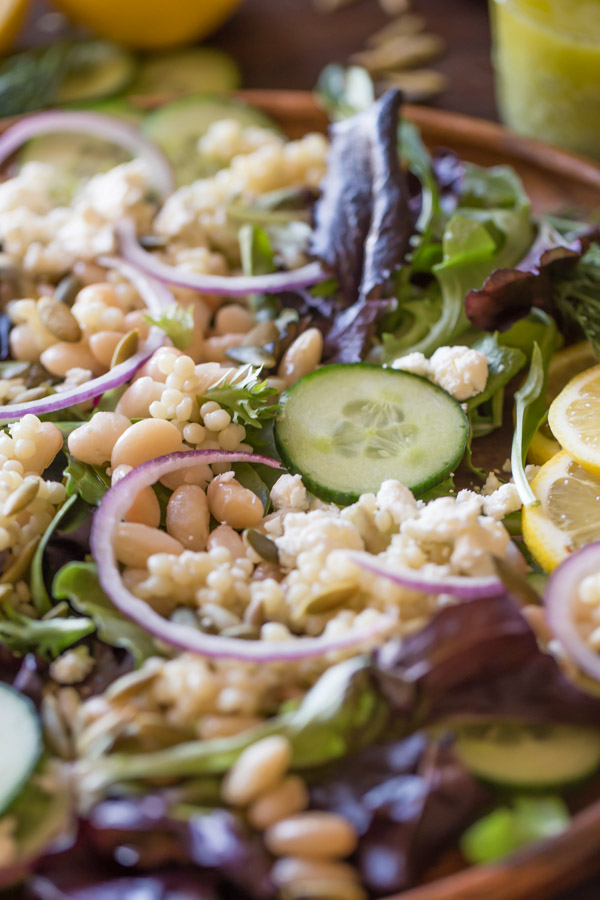White Bean Couscous Salad With Lemon Vinaigrette on a large wood plate.
