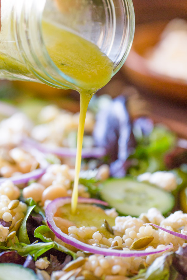 A glass jar of Lemon Vinaigrette being poured on top of the White Bean Couscous Salad.