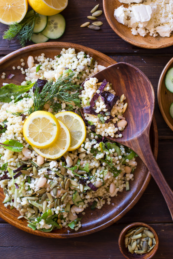 White Bean Couscous Salad With Lemon Vinaigrette on a large wood plate, garnished with lemon slices and fresh dill, with a wooden spoon in it, and a wood bowl of feta cheese next to it along with a cut lemon with fresh dill and cucumber slices, and a small wood bowl of pepitas.