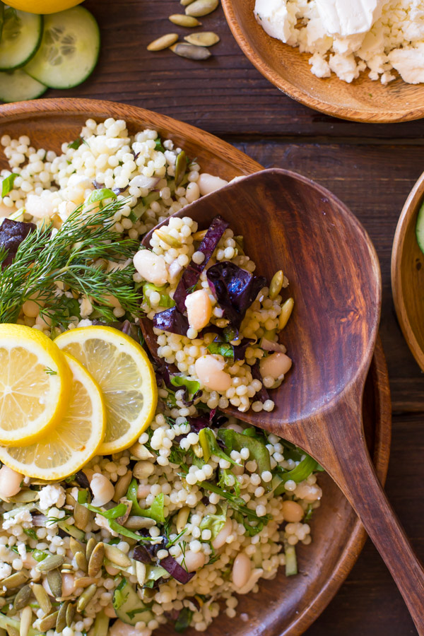 White Bean Couscous Salad With Lemon Vinaigrette on a large wood plate, garnished with lemon slices and fresh dill, with a wooden spoon in it and a wood bowl of feta cheese next to it.