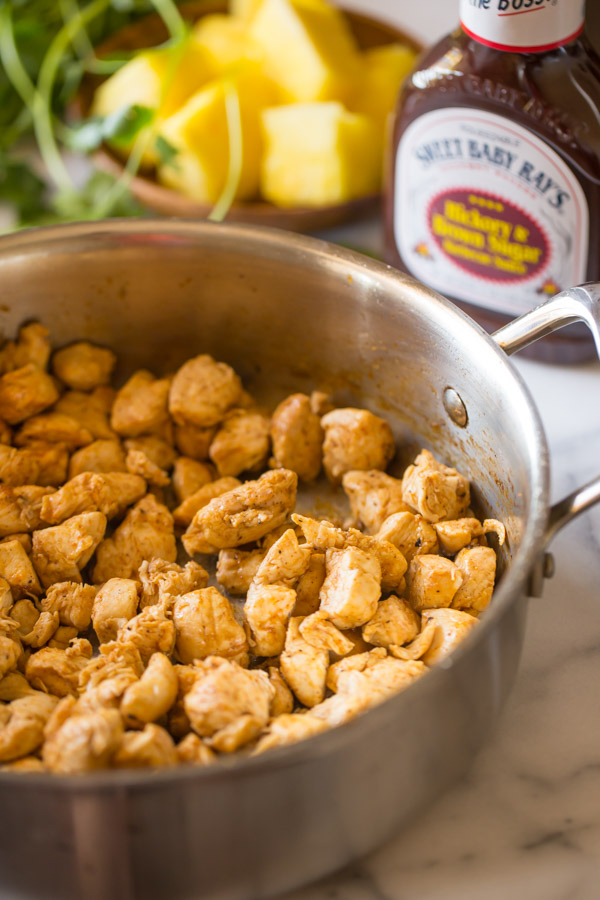 A large skillet with cooked chicken cubes in it, and a bottle of Sweet Baby Ray's Hickory and Brown Sugar Barbecue Sauce and a plate of pineapple chunks in the background.