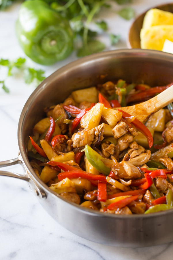 BBQ Chicken Fajitas in a large skillet with a wooden spoon in it, and a whole green paper and pineapple chunks in the background.