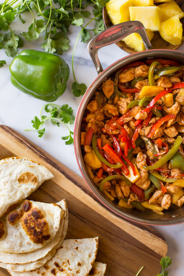 BBQ Chicken Fajitas in a large skillet, sitting next to a cutting board with browned tortillas, a whole green pepper, fresh cilantro and a plate of pineapple chunks.