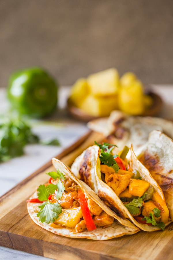 BBQ Chicken Fajitas in flour tortillas garnished with cilantro, on a cutting board, with a green pepper, fresh cilantro, and pineapple chunks in the background.