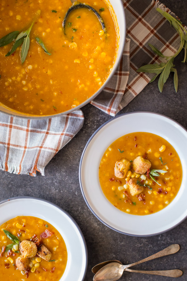 Two bowls of Butternut Squash Corn Chowder with Goat Cheese Croutons on top, sitting next to a large pot of Butternut Squash Corn Chowder.