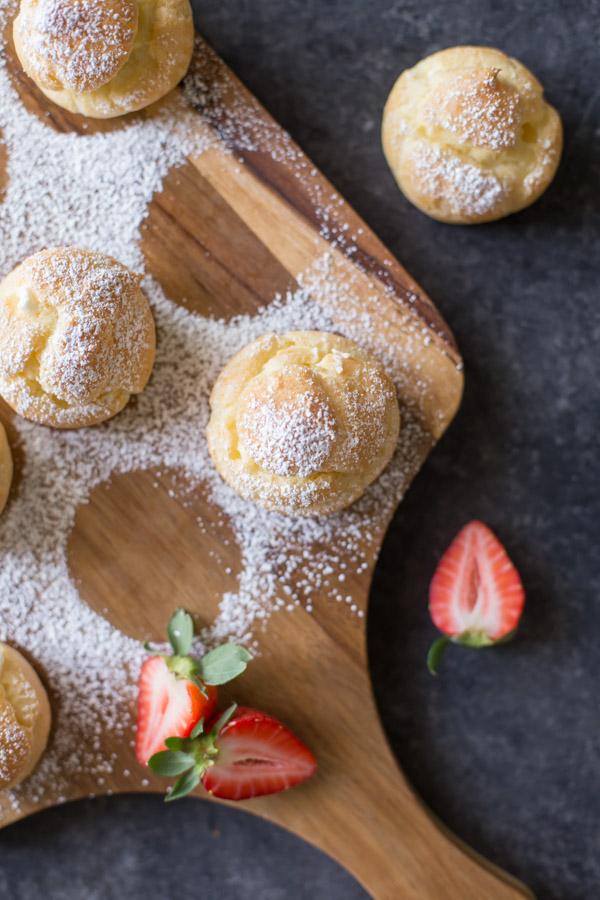 Classic Cream Puffs dusted with powdered sugar, sitting on a cutting board.