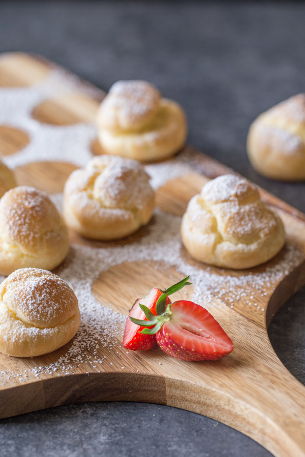 Classic Cream Puffs dusted with powdered sugar, sitting on a cutting board.