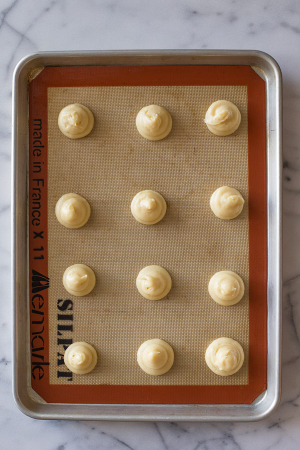 Classic Cream Puff dough that has been piped onto a Silpat lined baking sheet.