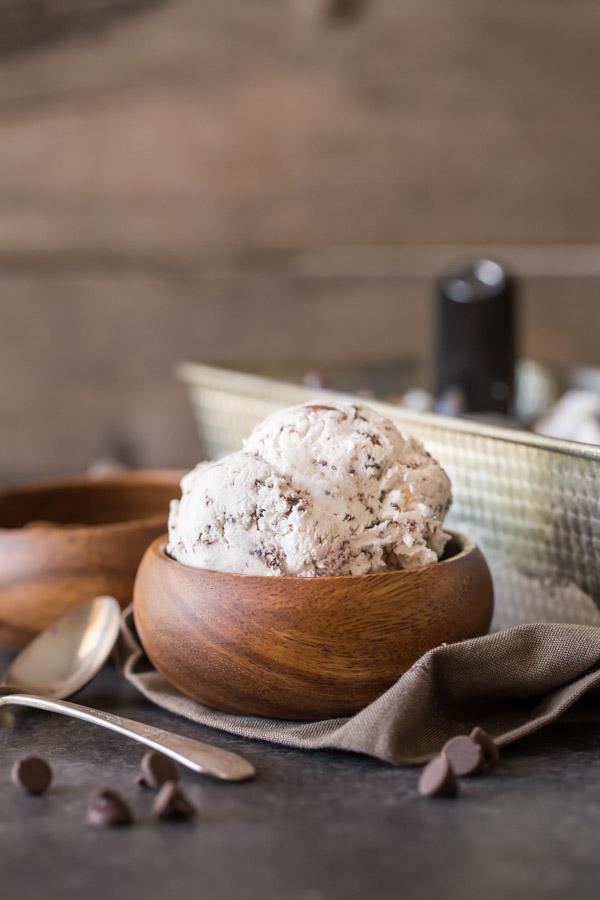 Dark Chocolate Almond Ice Cream in a small wood bowl, with a small wood bowl of almonds and a loaf pan of Dark Chocolate Almond Ice Cream in the background.