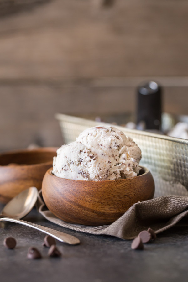 Dark Chocolate Almond Ice Cream in a small wood bowl, with a small wood bowl of almonds and a loaf pan of Dark Chocolate Almond Ice Cream in the background.