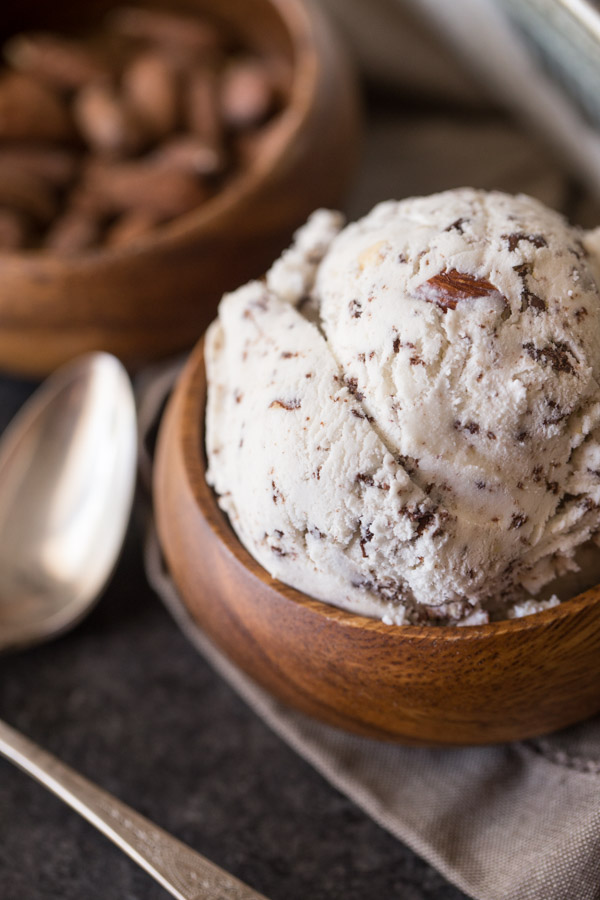 Dark Chocolate Almond Ice Cream in a small wood bow, with a wood bowl of almonds in the background.