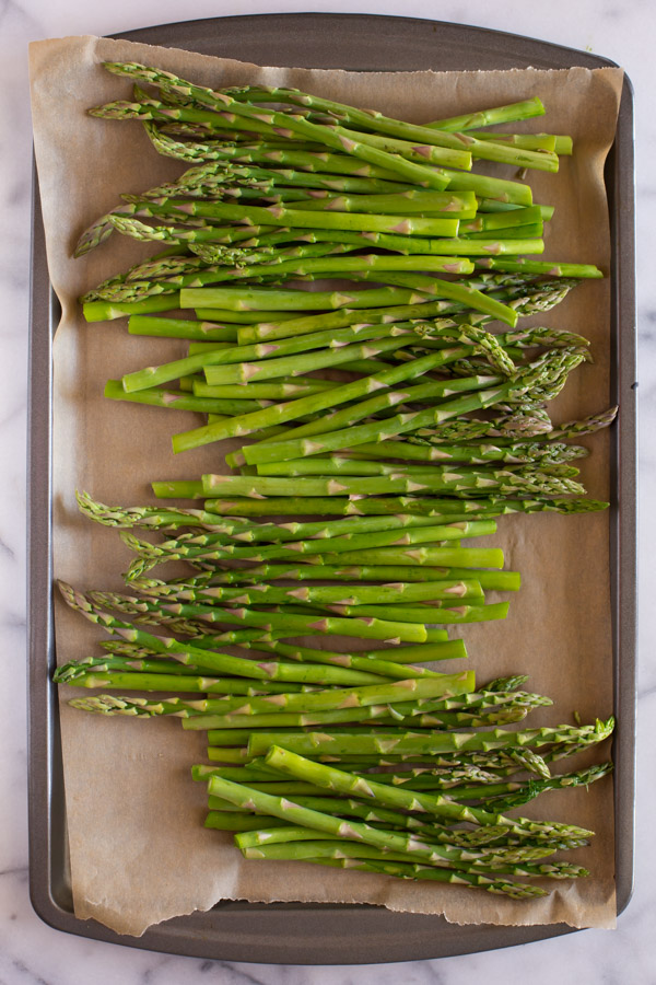 Trimmed asparagus on a parchment paper lined baking sheet.