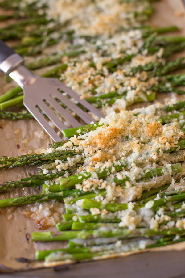 Roasted Asparagus With Panko and Gruyere on a parchment paper lined baking sheet with a spatula.