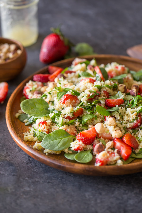 Strawberry Couscous Spinach Salad on a large wood plate, with a bowl of hazelnuts, a glass jar of almond vinaigrette and strawberries in the background.