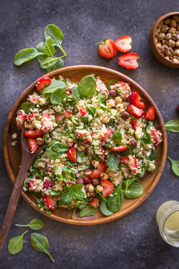 Strawberry Couscous Spinach Salad on a large wood plate with a wooden spoon it it, with spinach, strawberries, a bowl of hazelnuts and a glass jar of almond vinaigrette around the plate.