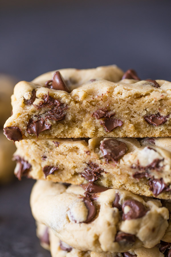 An Ultimate Chocolate Chip Cookie cut in half, stacked on top of two whole cookies.
