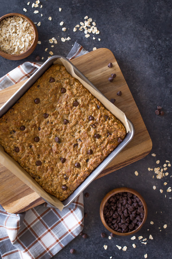 Whole Wheat Oatmeal Chocolate Chip Snack Bars in a parchment paper lined baking pan, with a wood bowl of oats and a wood bowl of chocolate chips next to the baking pan.