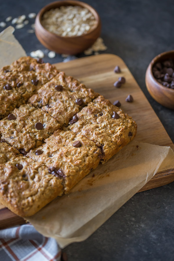 Whole Wheat Oatmeal Chocolate Chip Snack Bars on parchment paper sitting on a board, with a wood bowl of oats and a wood bowl of chocolate chips next to the board.