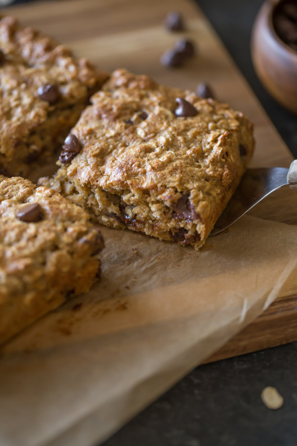 Whole Wheat Oatmeal Chocolate Chip Snack Bars on parchment paper sitting on a board, and a spatula under one of the bars.