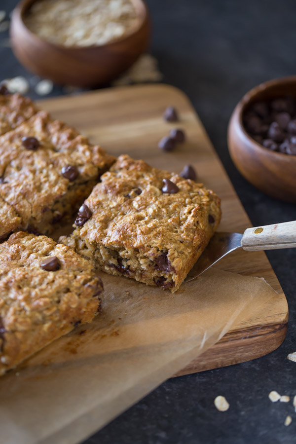 Whole Wheat Oatmeal Chocolate Chip Snack Bars on parchment paper sitting on a board, and a spatula under one of the bars, with a wood bowl of oats and a wood bowl of chocolate chips next to the board.