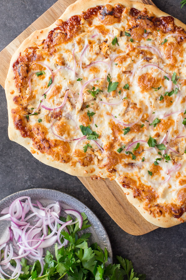 Barbeque Chicken Pizza on a cutting board, sitting next to a plate of flat leaf parsley and sliced red onions.