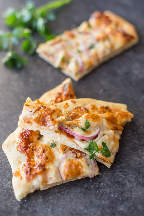Two slices of Barbeque Chicken Pizza, with another slice in the the background next to some flat leaf parsley.