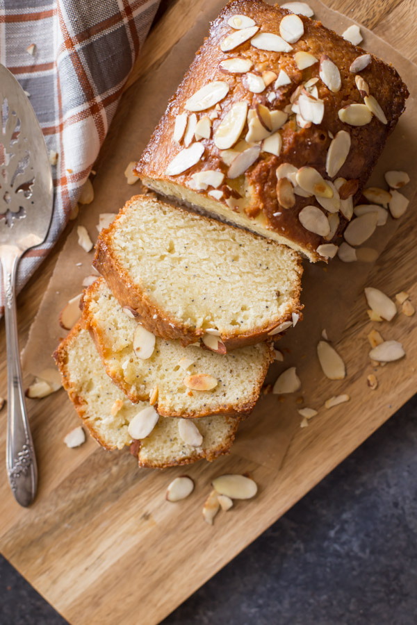 Glazed Almond Poppy Seed Bread sliced on a wood cutting board with a serving spatula next to it.