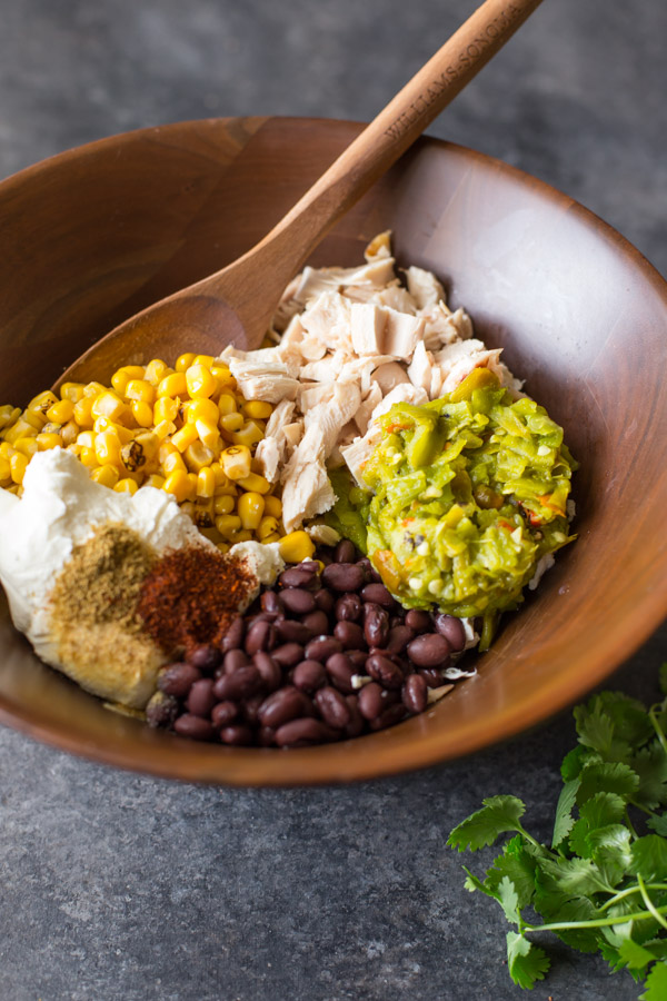 All the ingredients for the filling of the Hatch Green Chile Chicken Enchiladas in a large wood bowl with a wooden spoon in it.