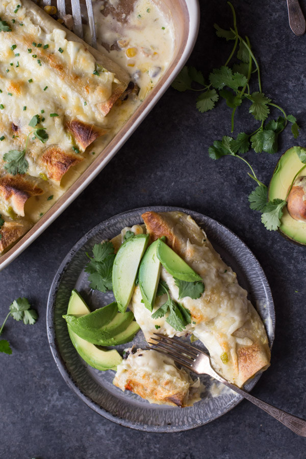 Hatch Green Chile Chicken Enchiladas on a plate with avocado slices, cilantro and a fork, sitting next to the baking dish of enchiladas.