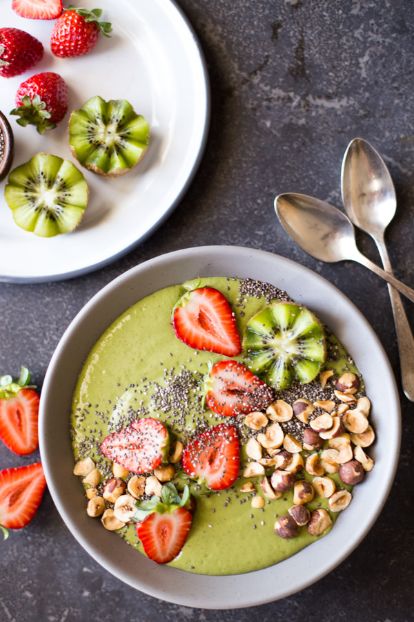 Strawberry Kiwi Protein Smoothie Bowl topped with sliced fresh strawberries and kiwi, hazelnuts, and chia seeds, with two spoons next to the bowl as well as a plate of strawberries and kiwi slices.